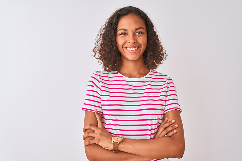 Young woman wearing pink striped t-shirt standing over isolated white background happy face smiling with crossed arms