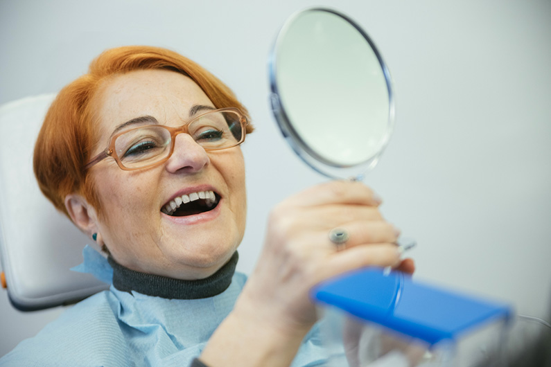 Senior Woman Sitting In A Chair Looking At Her Teeth In The Mirror