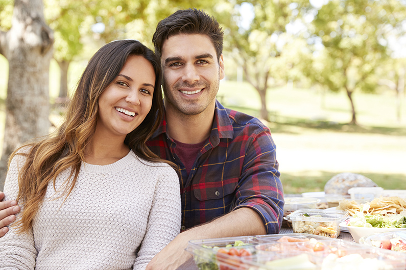 Young couple sitting at picnic table smiling to camera