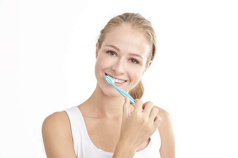Happy woman brushing her teeth
